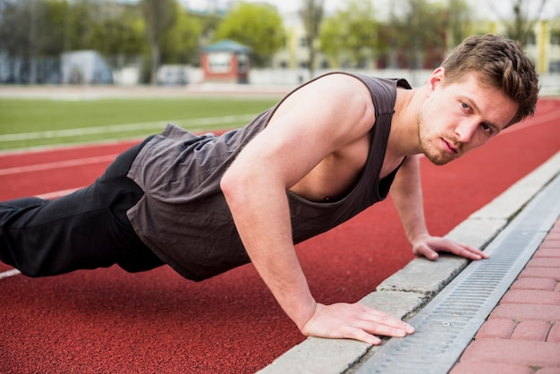 Handsome male athlete doing pushup on race track