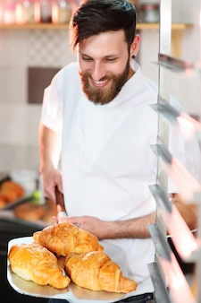 Handsome male baker holds a tray with french croissants in front of a bakery and smiles.
