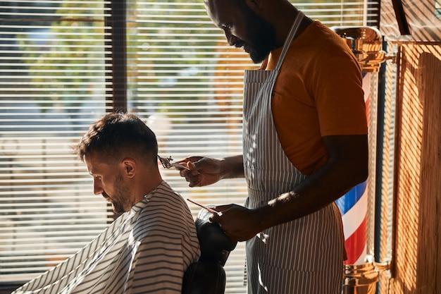 金属のバリカンでクライアントの髪を切るハンサムな男性の床屋