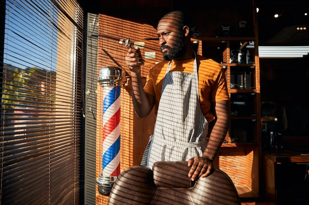 ポータブルバリカンを保持しているエプロンのハンサムな男性床屋