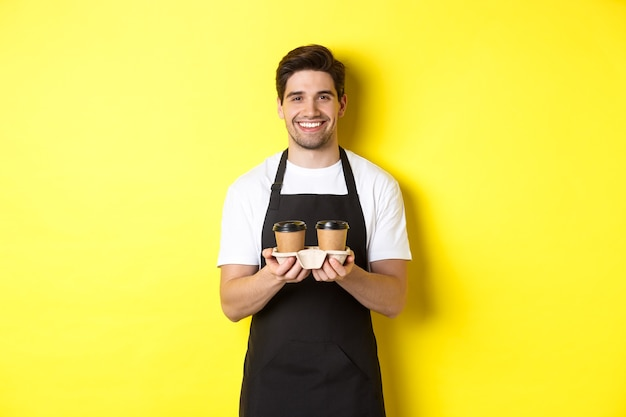 Handsome male barista serving takeaway coffee and smiling bringing order standing in black apron aga...