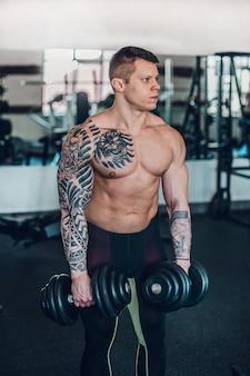 Красивый мужской культурист с гантелями, стоя в фитнес-зале