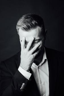 写真スタジオでポーズをとってスーツを着たハンサムな男性実業家。ハーフレングスのポートレート
