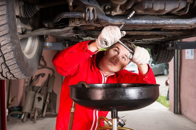 Handsome male car mechanic in uniform working underneath a lifted car