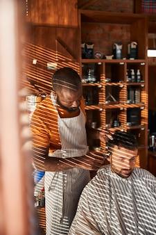 理髪店で散髪をしているハンサムな男性のクライアント