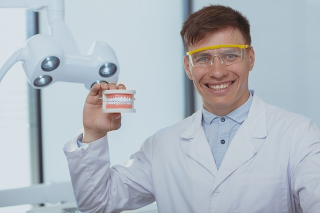Красивый мужской стоматолог работает в своей клинике