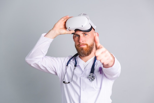 Bel medico maschio sul muro grigio in occhiali per realtà virtuale