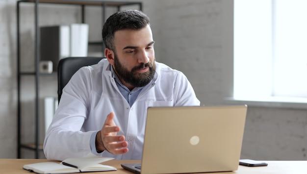 Красивый мужчина-врач имеет видеозвонок, видеочат, конференцию с коллегами или удаленный пациент онлайн с помощью веб-камеры на ноутбуке.