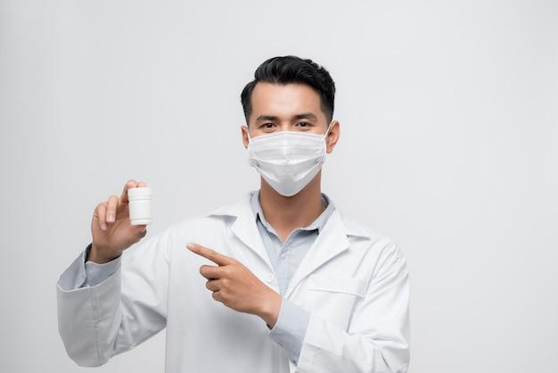 Красивый мужской доктор держа пустую белую или пустую бутылку таблеток. стоя изолированные на белом фоне