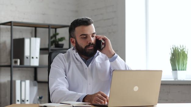 オフィスのハンサムな男性医師がスマートフォンで患者と会話しています。