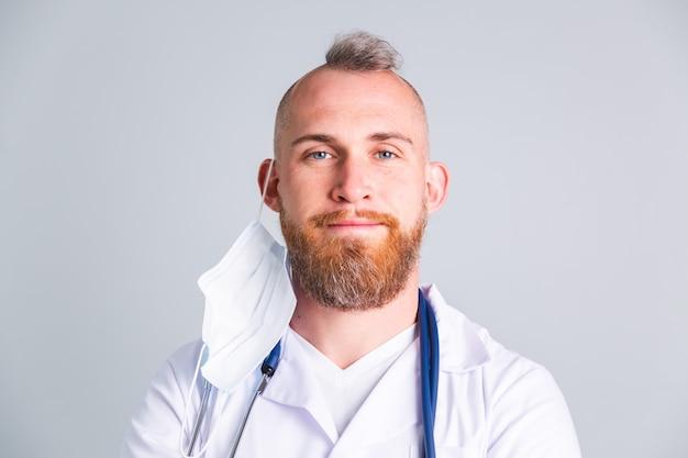 회색 벽에 잘 생긴 남자 의사는 보호 의료 마스크를 벗고