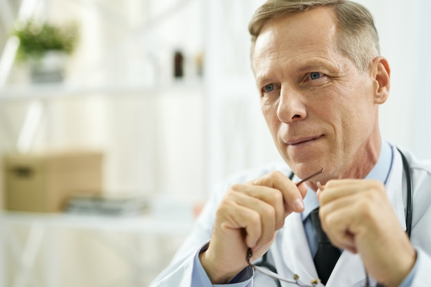 Handsome male doctor with glasses in his hands