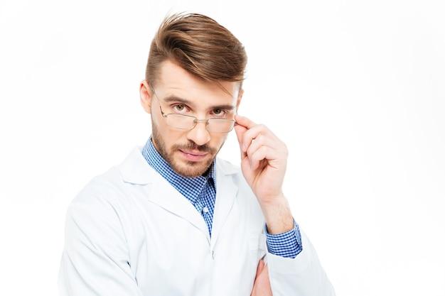 白い背景で隔離のカメラを見て眼鏡をかけてハンサムな男性医師