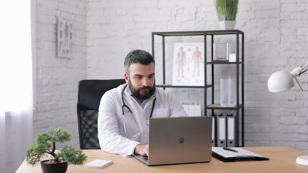 診療所でラップトップを使用して作業しているハンサムな男性医師