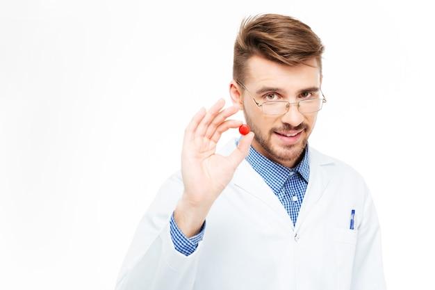白い背景で隔離の赤い丸薬を保持しているハンサムな男性dotor