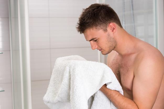 Красивый мужчина вытирает лицо чистым полотенцем после процедуры умывания в современной, облицованной кафелем ванной комнате
