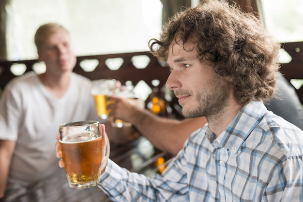 Handsome male drinking beer near friends in bar
