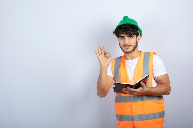 Handsome male engineer in green hardhat with notebook standing over white wall. high quality photo