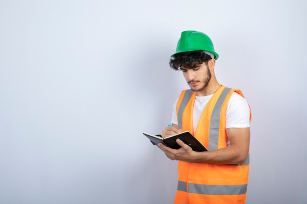 Handsome male engineer in hardhat writing on notebook over white wall. high quality photo