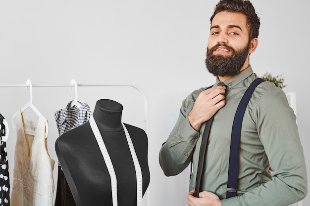 Handsome male fashion designer posing in atelier with dress form