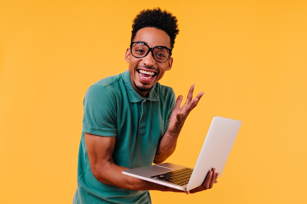 Handsome male freelancer in glasses smiling. ecstatic african student holding laptop and expressing happiness.