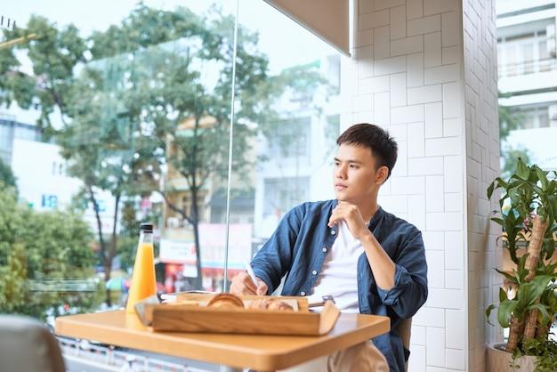 잘 생긴 남성 프리랜서 작가가 카페에 앉아 아침에 열심히 일하면서 출판을 마치기 전에 일기에 최고의 아이디어를 기록하는 마케팅 회사의 광고 기사를 작성합니다.
