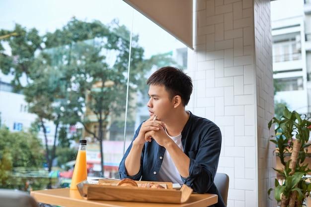 マーケティング会社の広告記事を作成しているハンサムな男性のフリーランサーライターが、カフェに座って朝に一生懸命働いてリリースから出版を終える前に、日記に最高のアイデアを記しています