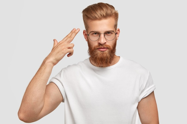 Handsome male hipster with gingerr beard and stubble, dressed in casual white t-shirt, makes suicide gesture, shoots in temple, feels tired of problems and difficult life, isolated over wall