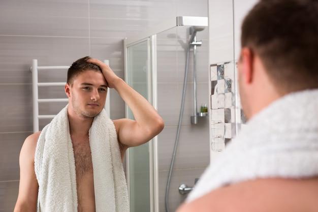 거울을 보고 현대적인 타일 욕실에 서 있는 동안 절차를 씻은 후 어깨에 수건을 들고 있는 잘생긴 남성