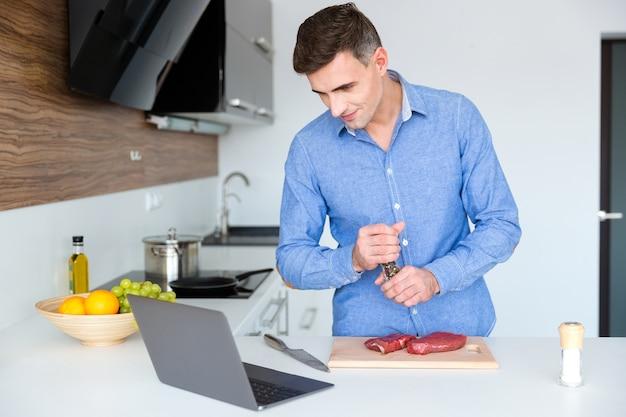 ラップトップで料理のレッスンを見て、キッチンで肉を準備する青いたわごとのハンサムな男性