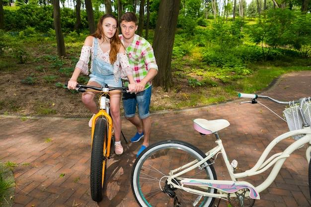 녹색과 빨간색 체크무늬 셔츠를 입은 잘생긴 남자는 공원에서 자전거를 타는 여자친구를 가르친다
