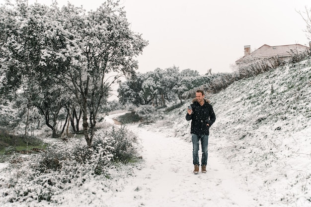 Красивый мужчина в верхней одежде стоит в заснеженном зимнем лесу и обменивается сообщениями на смартфоне