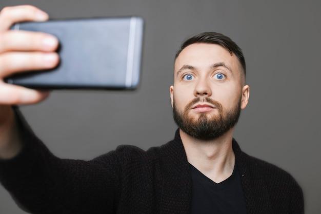 スマートフォンを保持し、灰色の背景で自分撮りのポーズをしながらカメラを見ているスタイリッシュな服装のハンサムな男性