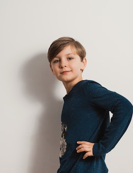 Handsome male kid standing by white wall, smiling