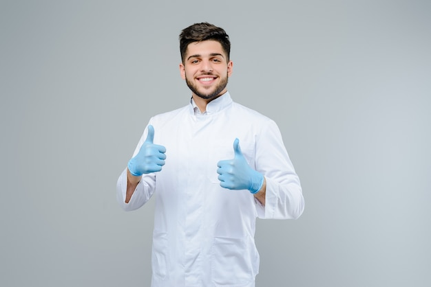 Handsome male medical doctor in gloves shows thumbs up isolated over grey background