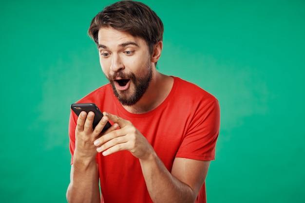 Красивый мужской модель с бородой с телефоном позирует в студии