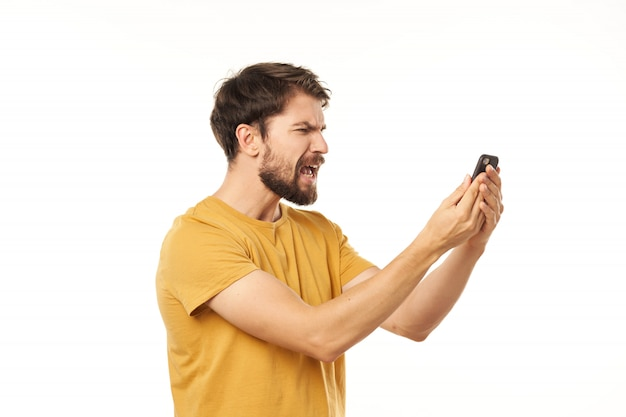 Handsome male model with beard with a phone posing in studio
