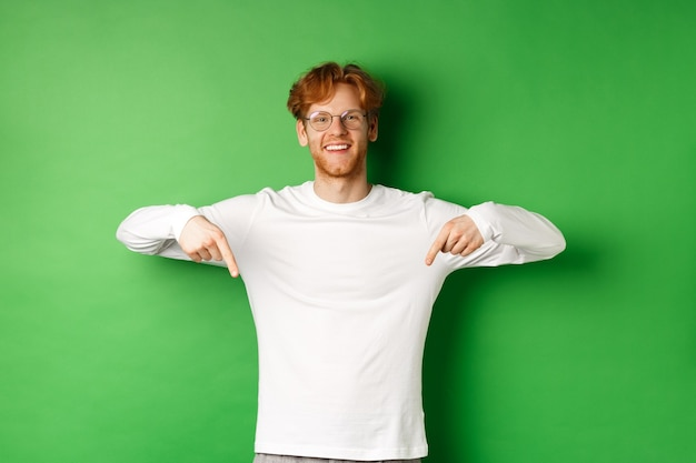 Handsome male model with red hair, wearing glasses and long-sleeve, pointing fingers down and smiling cheerful, showing promo, green background.