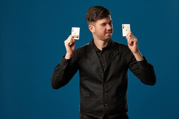 잘 생긴 남성, 포커에 멍청한 놈, 검은 조끼와 셔츠. 두 개의 카드 놀이를 들고 웃 고 그것을 보고 있습니다. 블루 스튜디오 배경 포즈. 도박, 카지노. 확대.