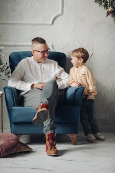 Handsome male person expressing positivity while sitting on armchair and listening to his son