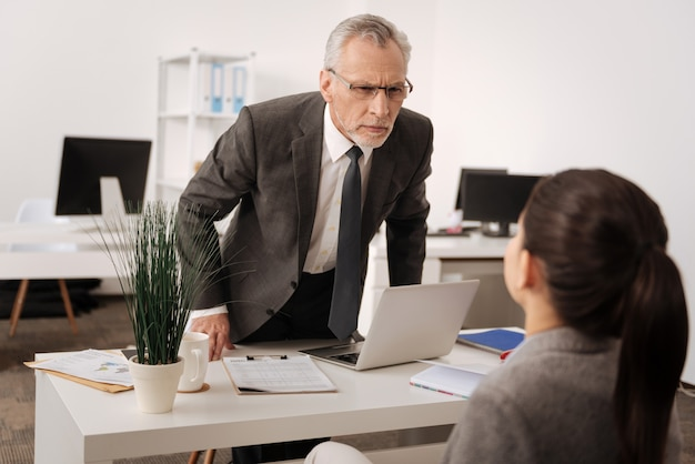 Handsome male person standing at his workplace opposite his coworker leaning on table while looking attentively at young woman