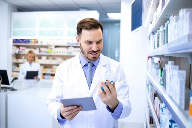 약국 상점이나 약국에서 약을 들고 태블릿 컴퓨터에서 가격을 확인하는 흰색 코트에 잘 생긴 남성 약사.