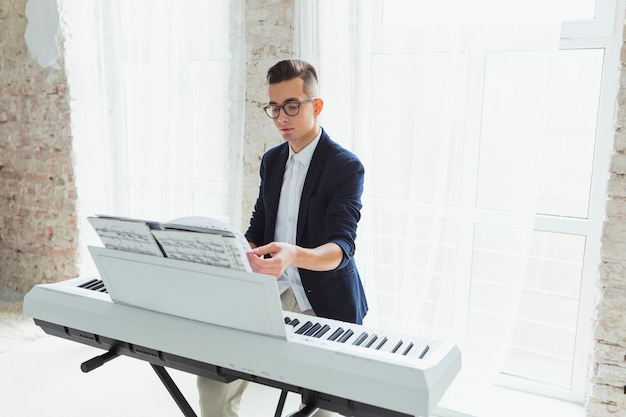 Handsome male piano player turning the pages of musical sheet on piano
