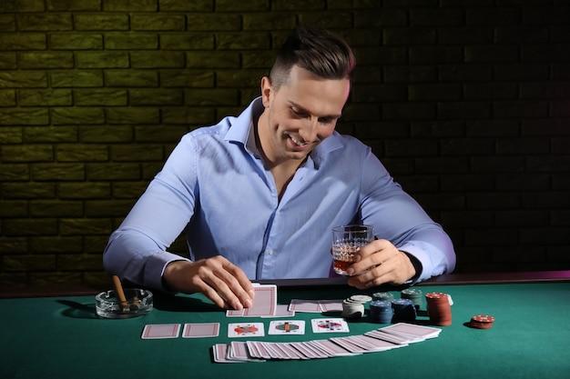 Красивый мужской игрок за столом в казино