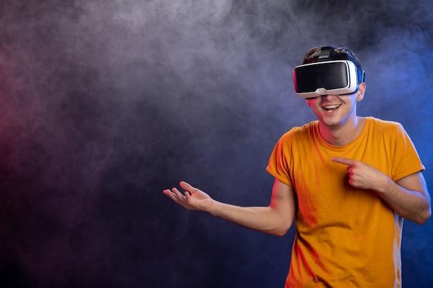 Красивый мужчина играет в игру в виртуальной реальности на темной поверхности