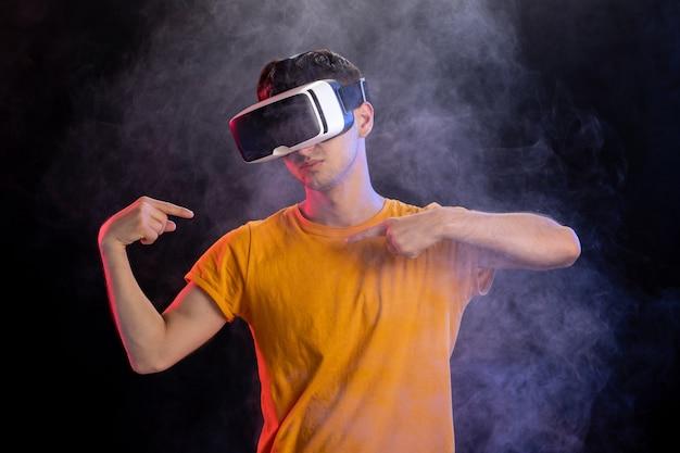 暗い表面の仮想現実でゲームをプレイするハンサムな男性