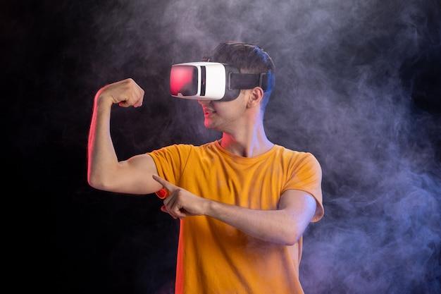 Bel maschio gioco di gioco nella realtà virtuale sulla superficie scura