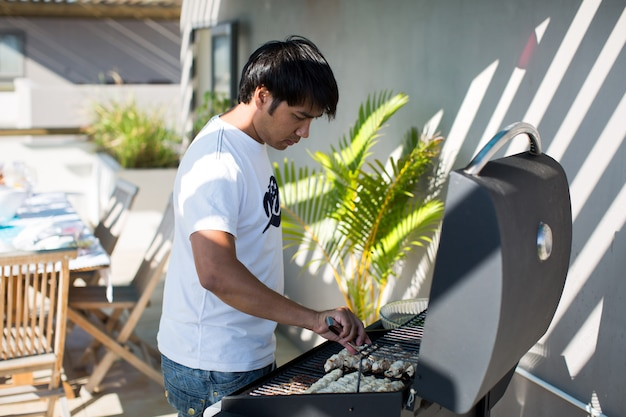 Handsome male prepares barbecue outdoors