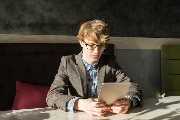 Handsome male reads tablet pc at cafe