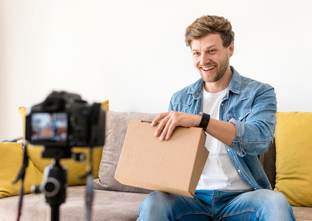 Handsome male recoding unboxing video at home